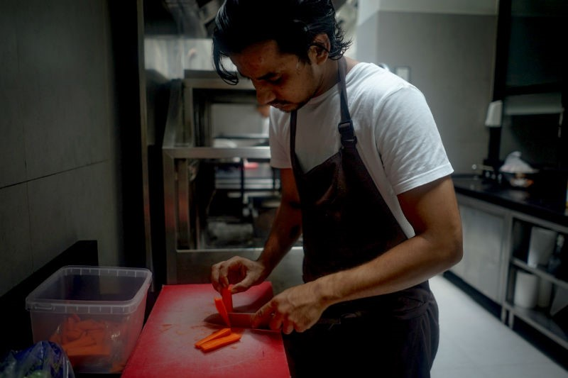 un commis coupe des carotte dans la cuisine